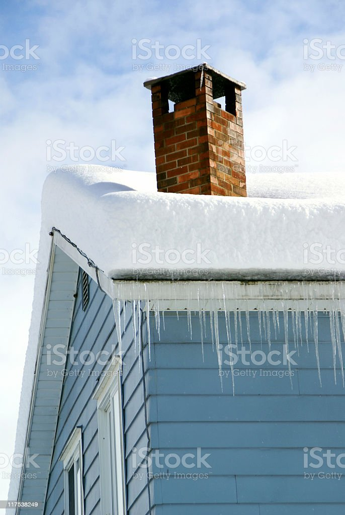 Snow Covered Rooftop with Chimney and Icicles stock photo