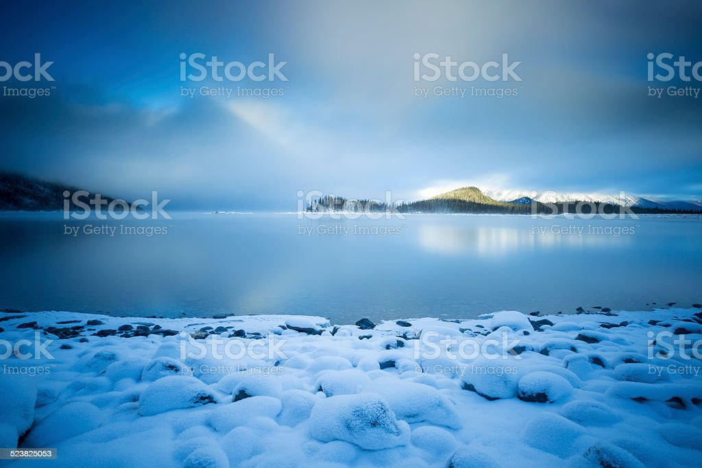 Snow Covered Shore on a Mountain Lake stock photo