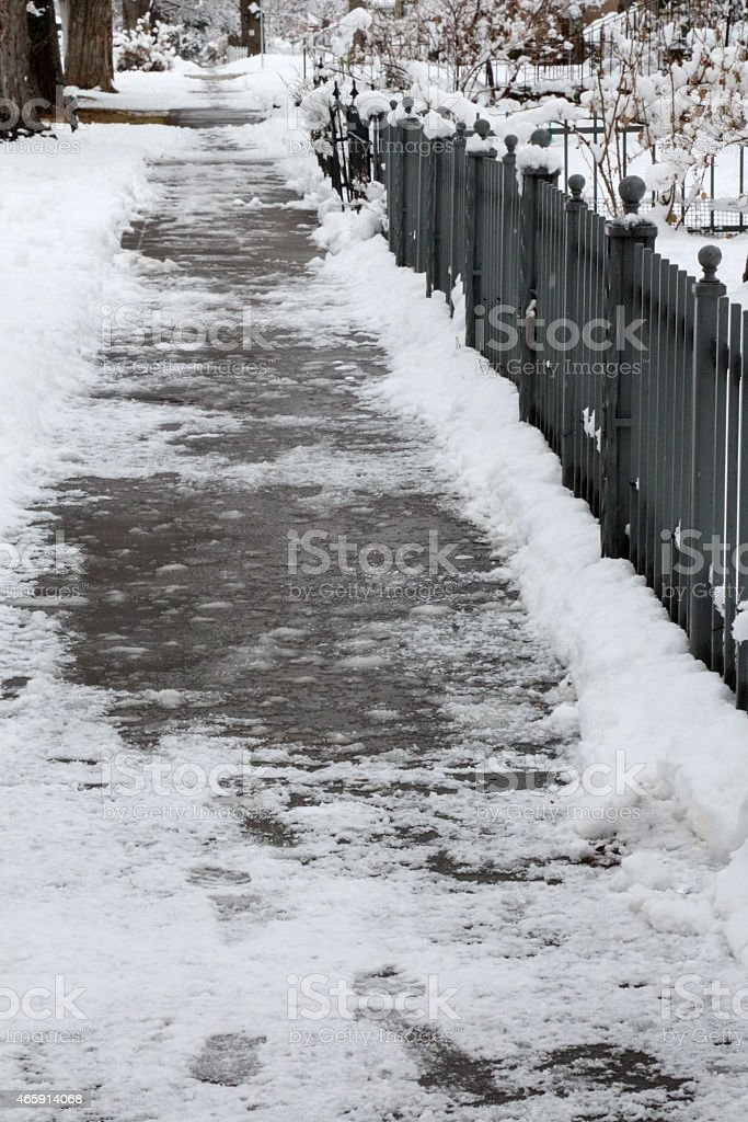 Snow covered sidewalk and wrought iron fence stock photo