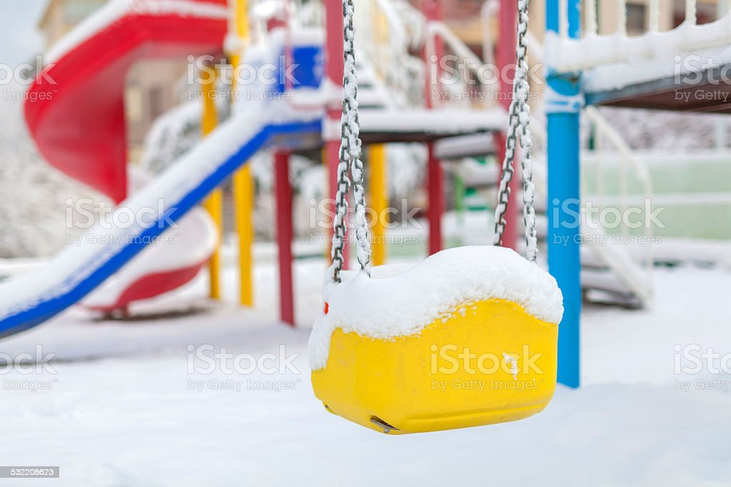 snow covered swing and slide at playground in winter stock photo