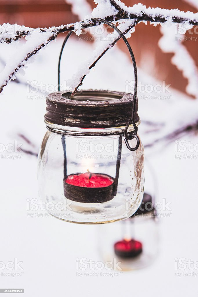 Snow covered tree branches with Christmas lanterns stock photo