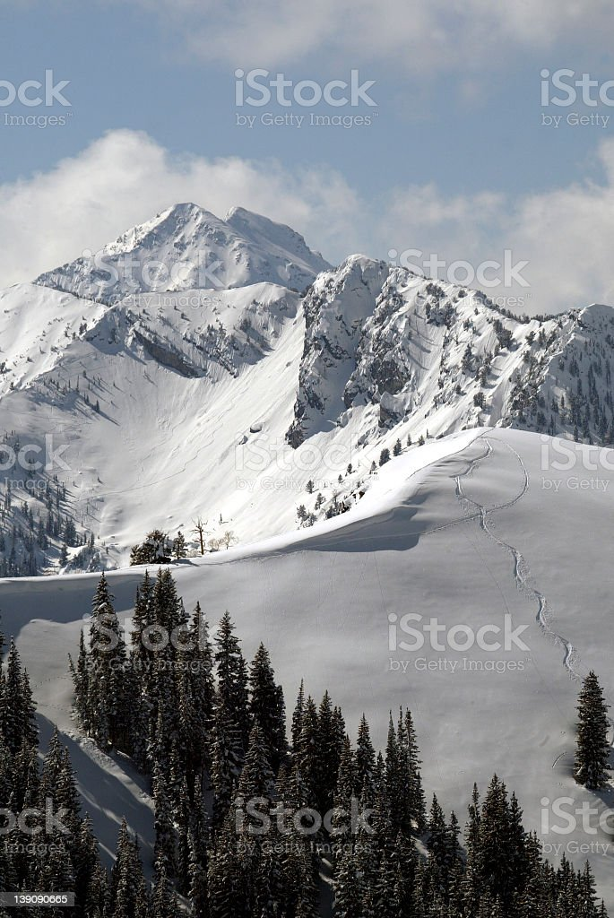 Snow covered Wasatch Mountains with cloudy blue sky stock photo