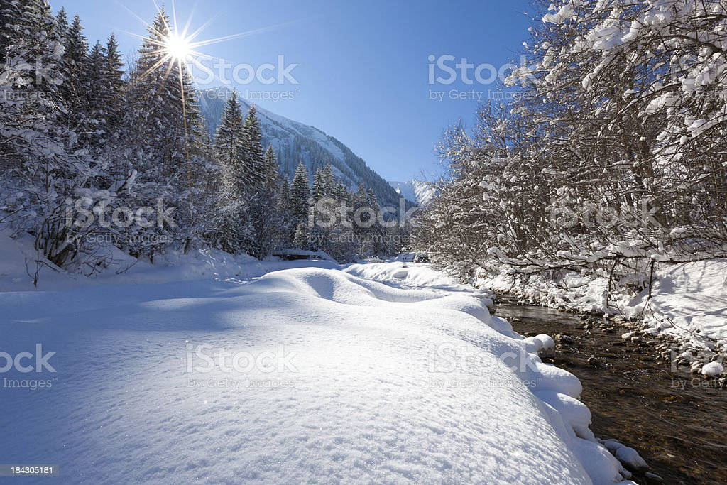 snow covered winter landscape in tirol with river, austria stock photo