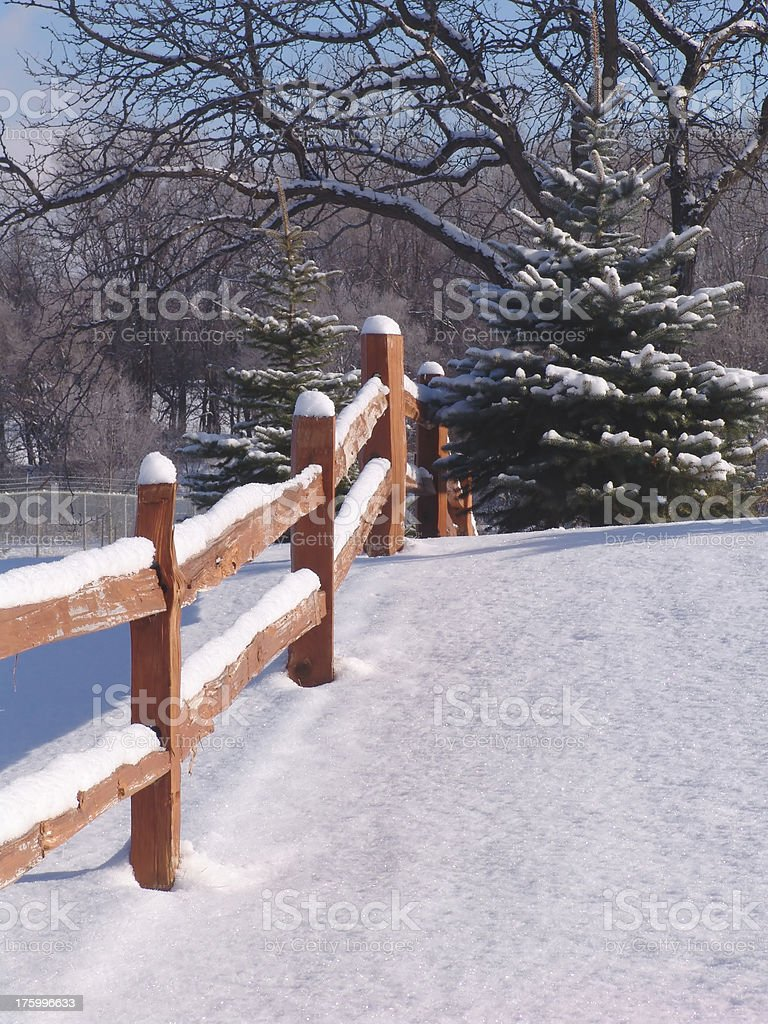 snow covered wooden fence in winter scene with trees royalty-free stock photo