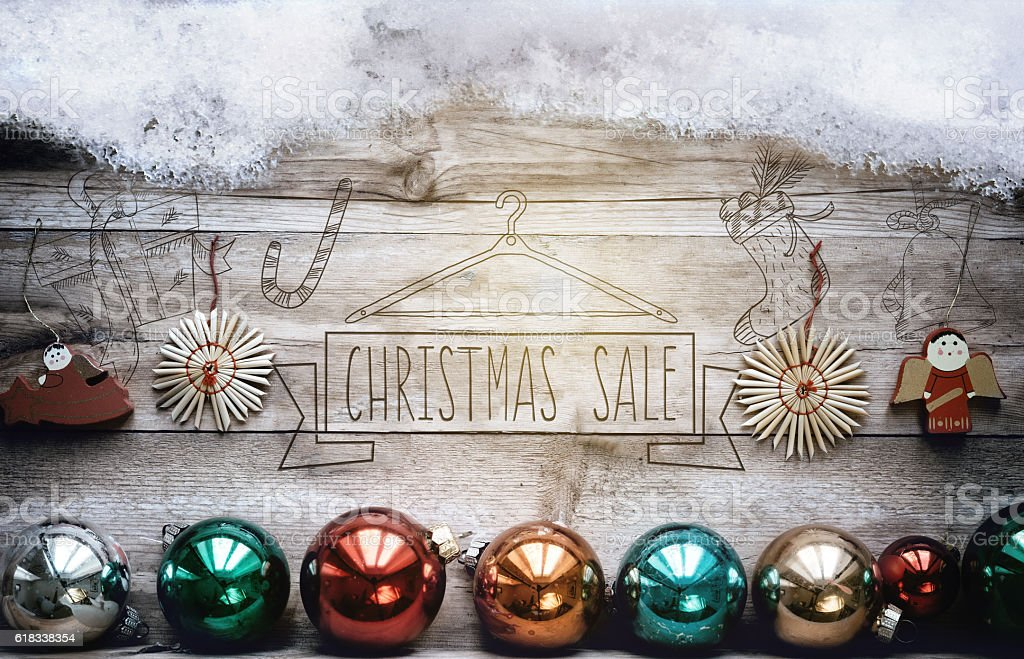 snow cropped wooden planks with christmas sale embossing and balls stock photo