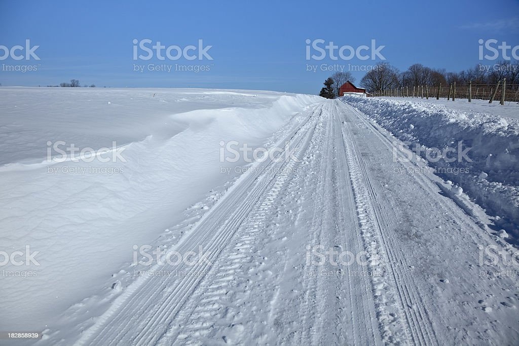 Snow Drifts on a Snowy Country Road Under Blue Sky stock photo