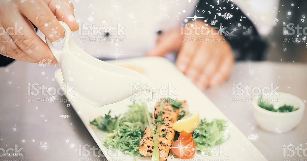 Snow falling against chef pouring sauce on salmon dish stock photo