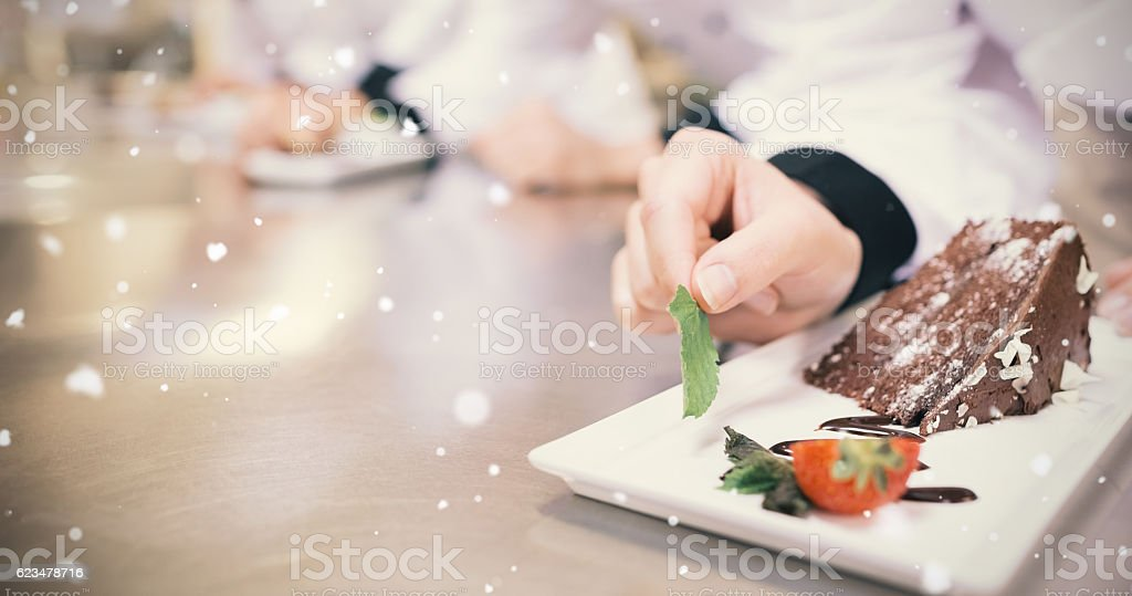 Snow falling against chocolate cake being garnished stock photo