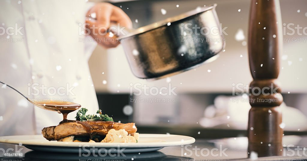 Snow falling against closeup of a chef garnishing food stock photo