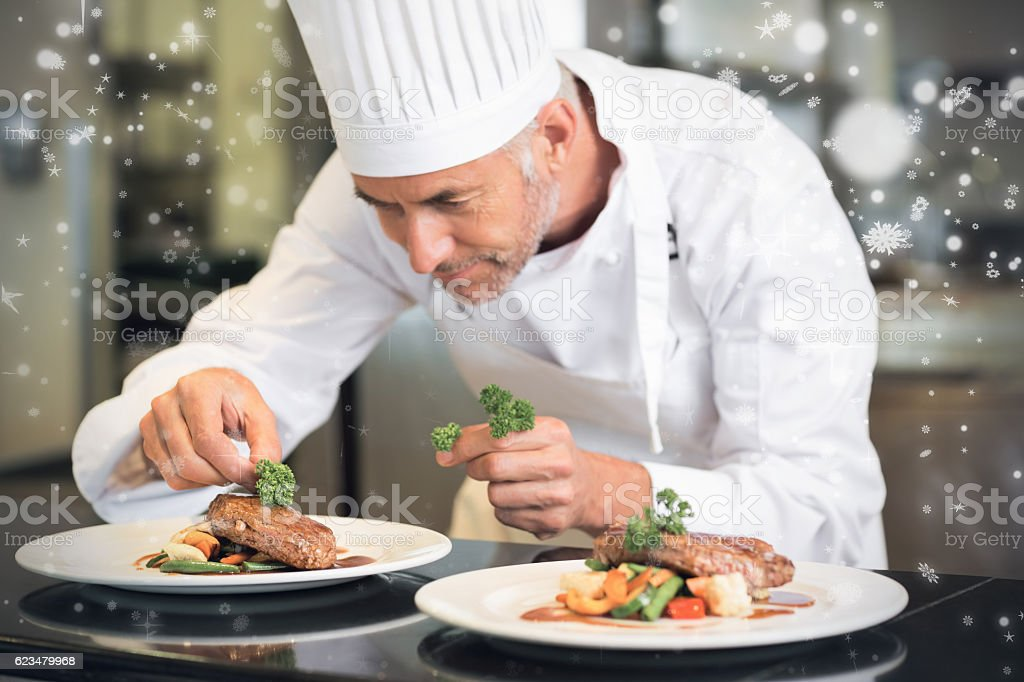 Snow falling against concentrated male chef garnishing food in kitchen stock photo