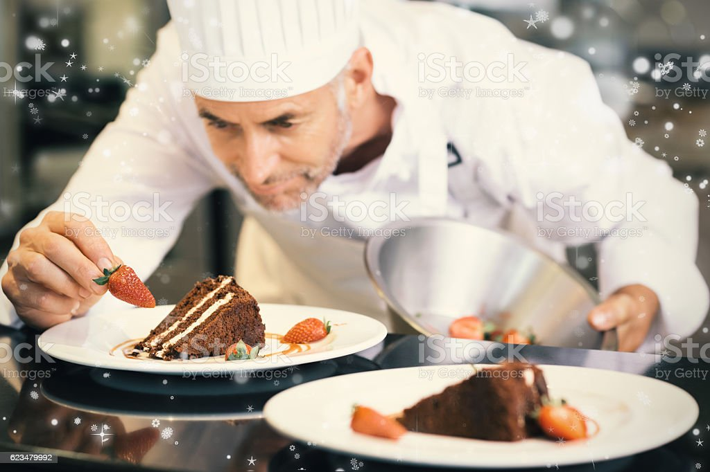 Snow falling against concentrated male pastry chef decorating dessert stock photo