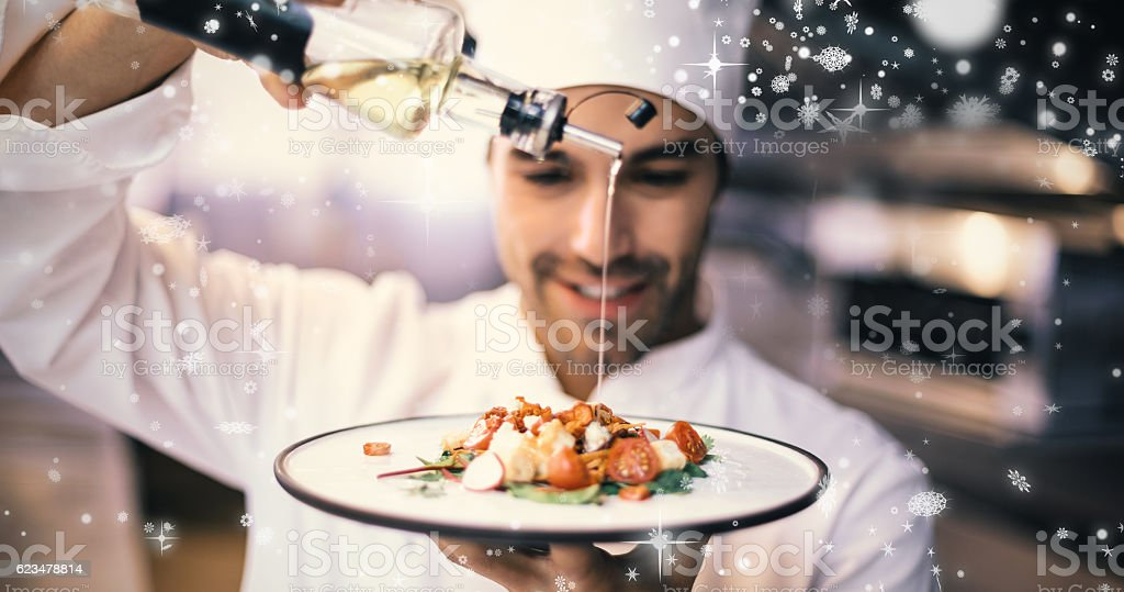 Snow falling against handsome chef pouring olive oil on meal stock photo