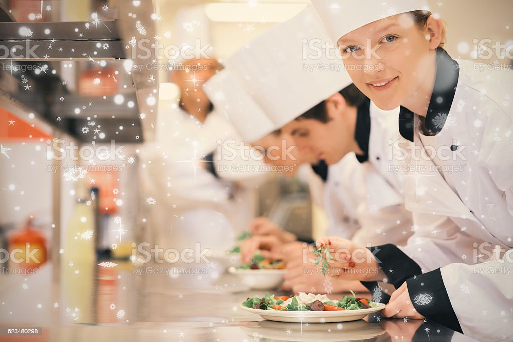 Snow falling against happy chef looking up from preparing salad stock photo