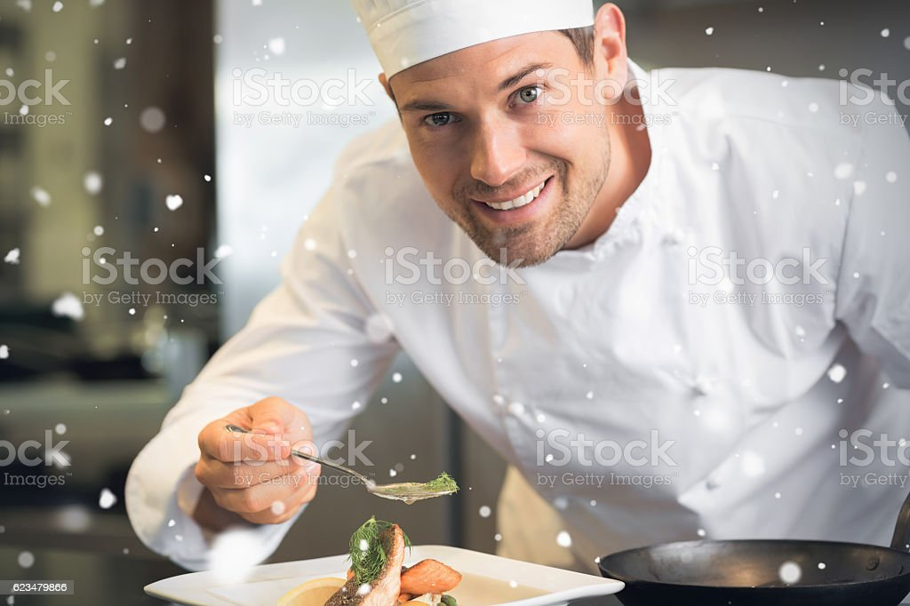 Snow falling against smiling male chef garnishing food in kitchen stock photo