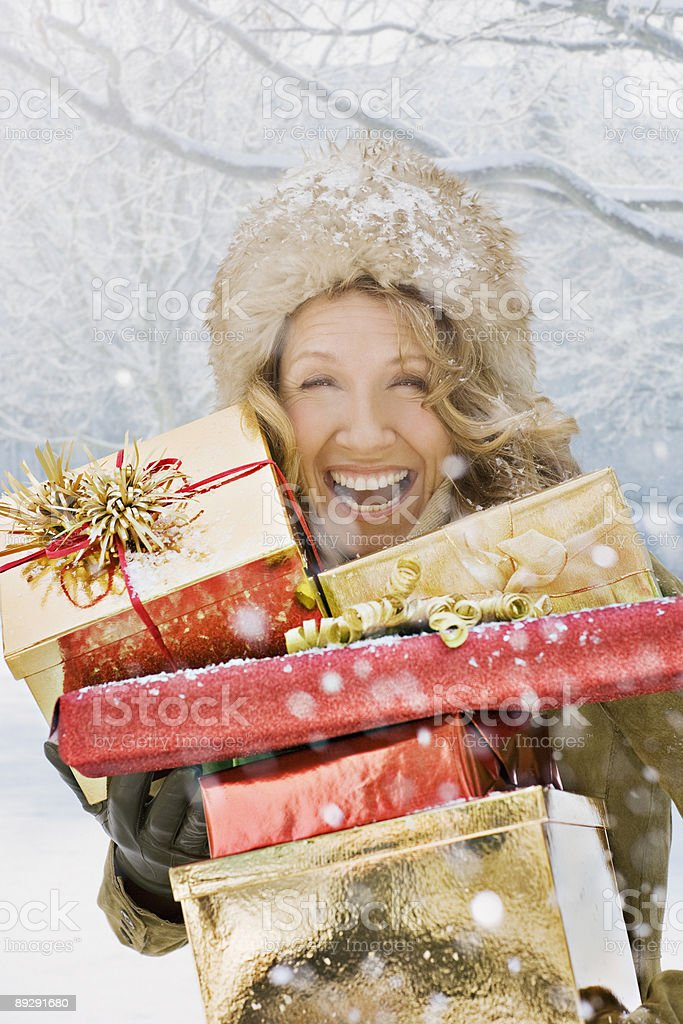 Snow falling on laughing woman holding Christmas gifts stock photo
