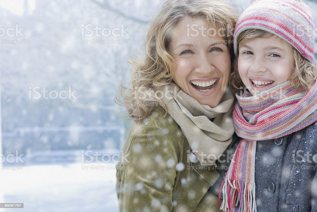 Snow falling on smiling mother and daughter royalty-free stock photo