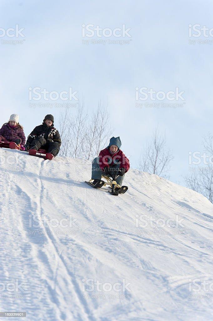 Snow gliding children glissade winter toboggan, sledging stock photo