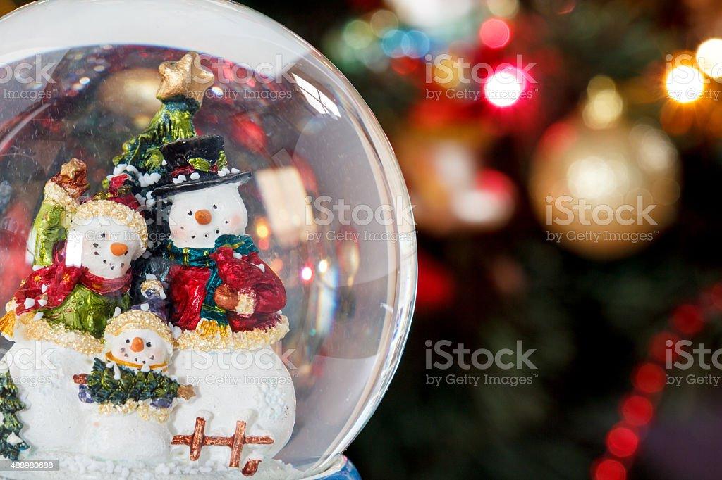 Snow globe with happy snowman family stock photo