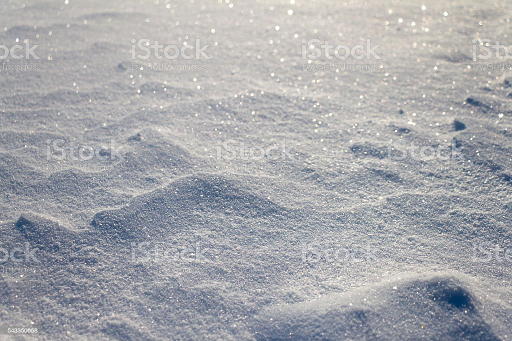 Snow grains close up. Blurred in the distance. stock photo