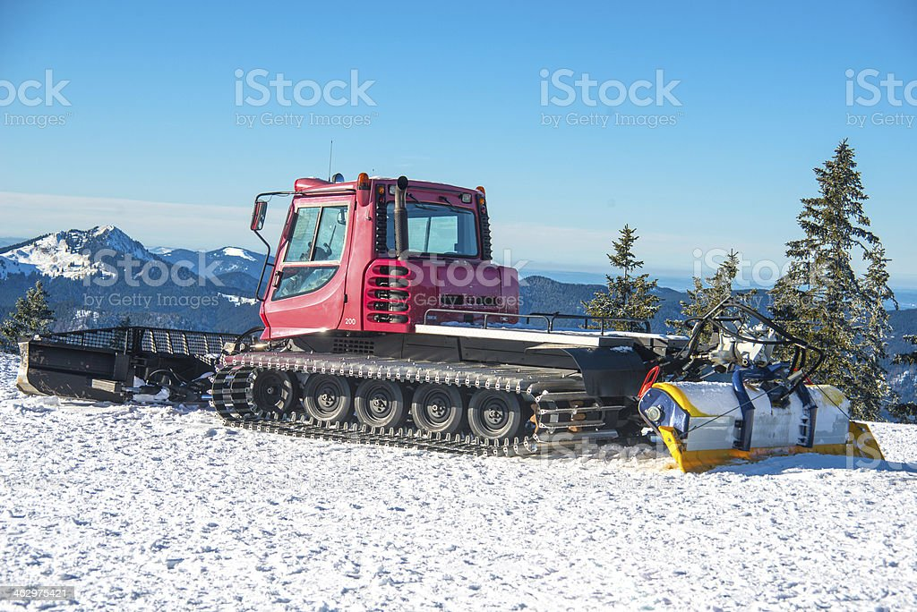 Snow groomer snowcat on mountain with and blue sky Pistenraupe stock photo