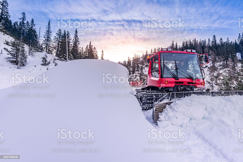 Snow groomer vehicle clearing snow off the road stock photo