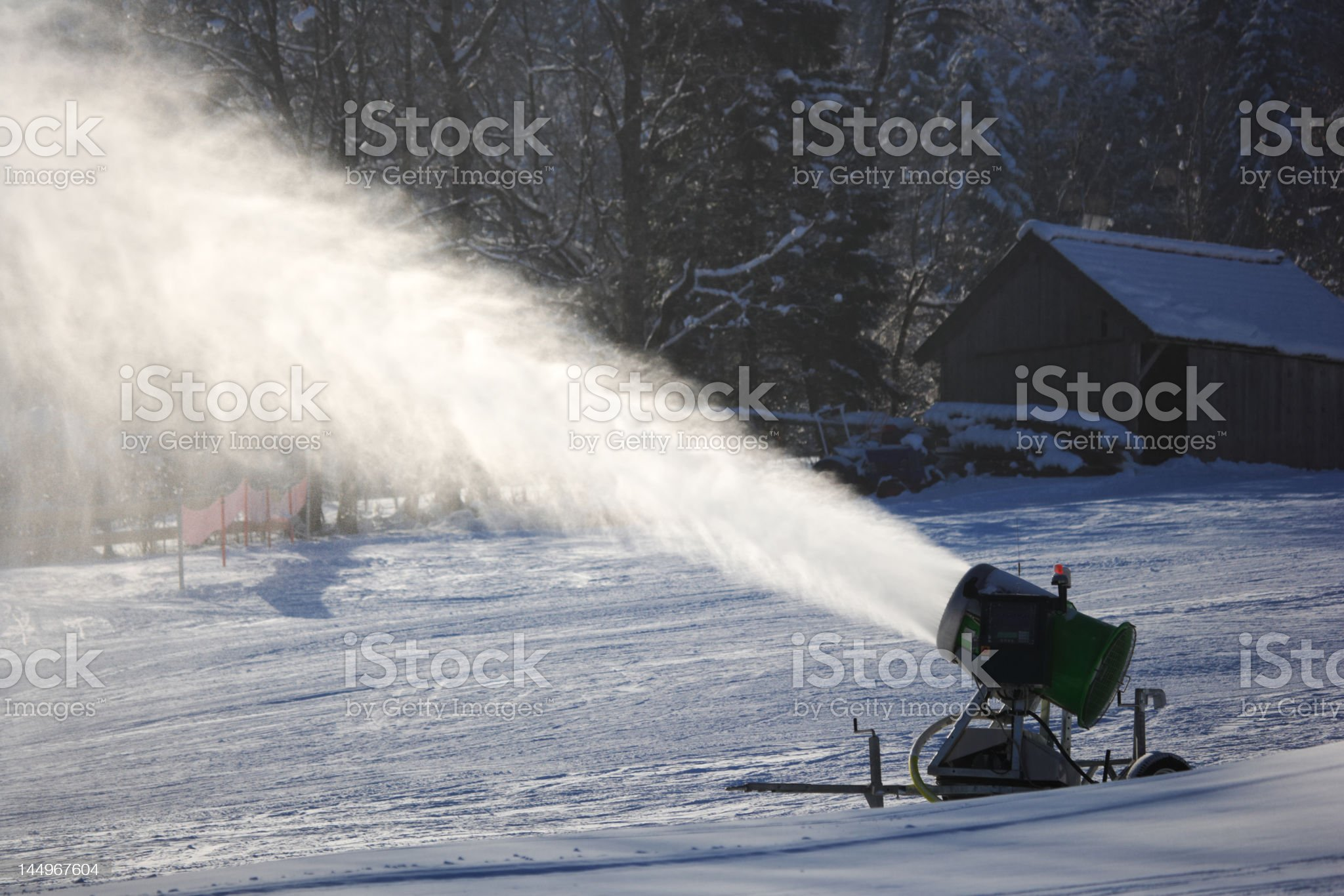 snow gun spraying on ski slope, back lit royalty-free stock photo