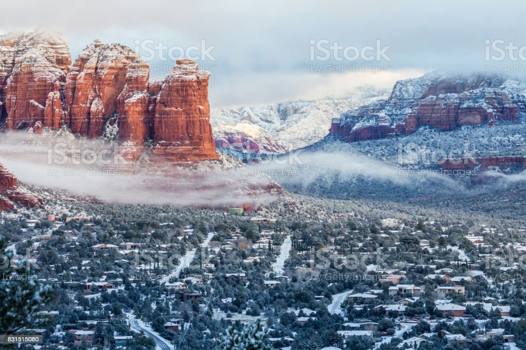 Snow highlights Sedona roads and rock layers of red mountains stock photo