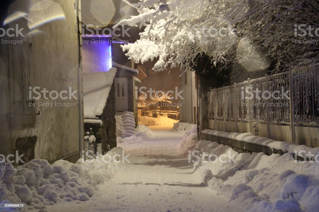 Snow in village street at night in Pyrenees stock photo