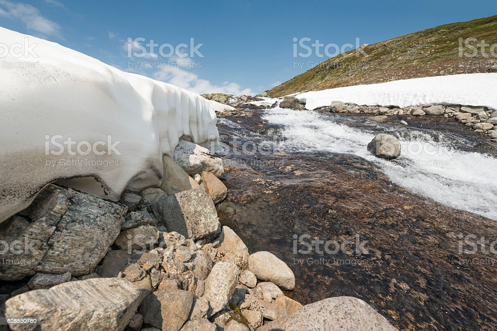 Snow is finally melting in Norwegian summer mountains stock photo
