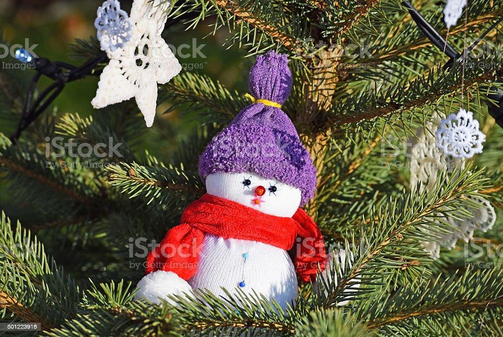 Snow man figurine in the christmas tree stock photo