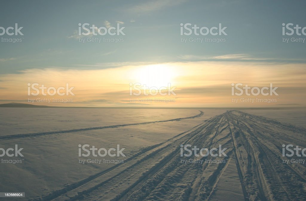snow mobile tracks across a frozen river at sunset royalty-free stock photo