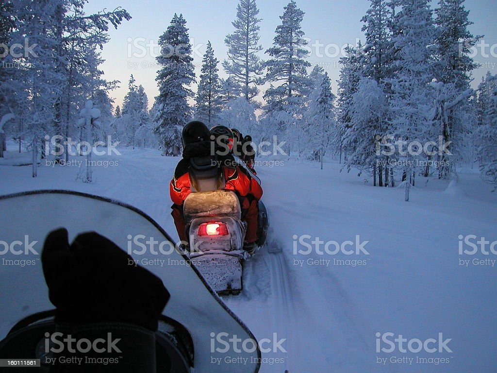 Snow mobiles driving through the thick snow entering forest stock photo