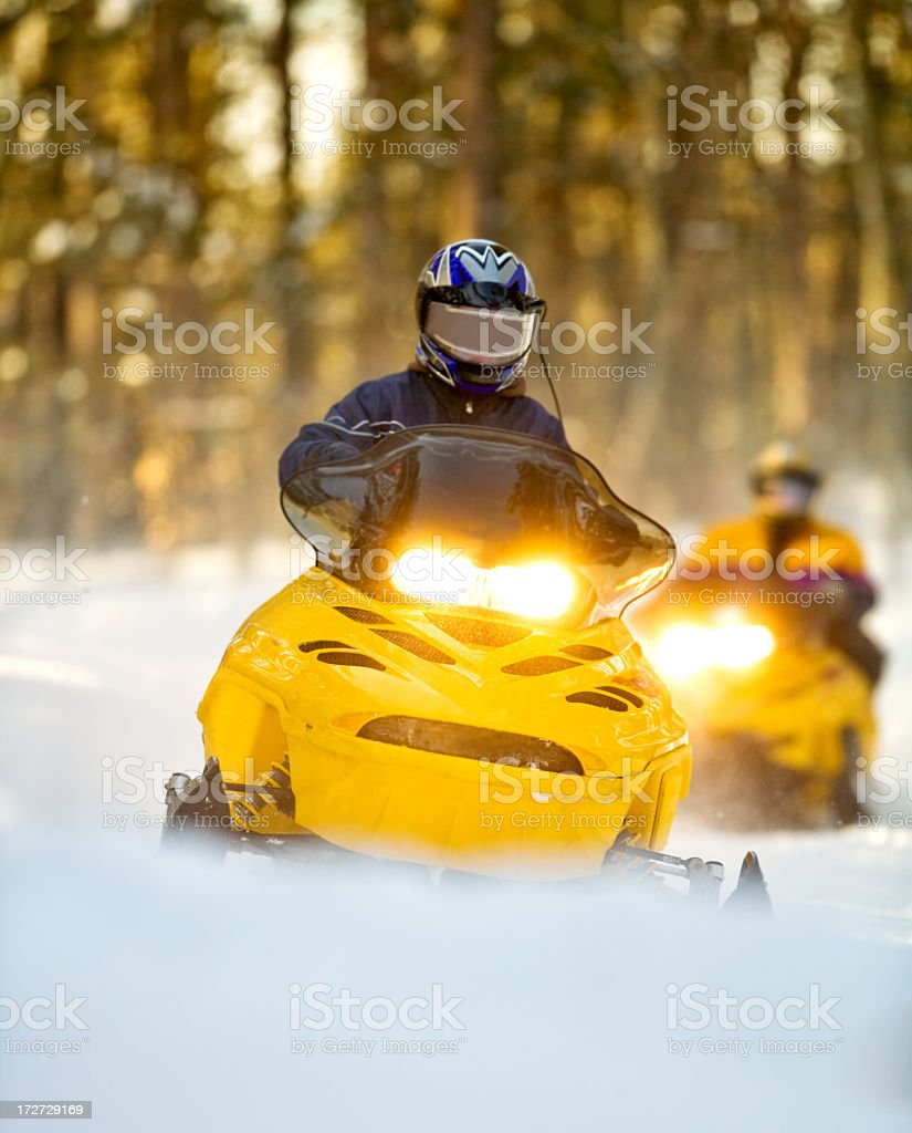 Snow mobiles with their lights on driving through the snow stock photo