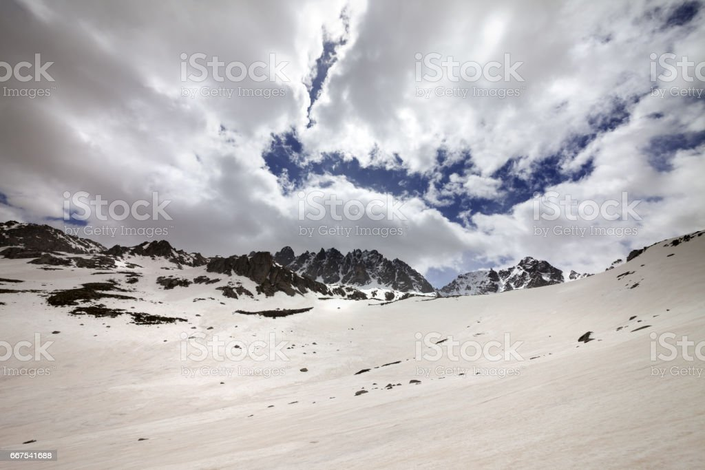 Snow mountain and cloud sky in gray spring day stock photo