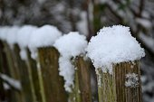 snow on an old fence in the park in the late autumn