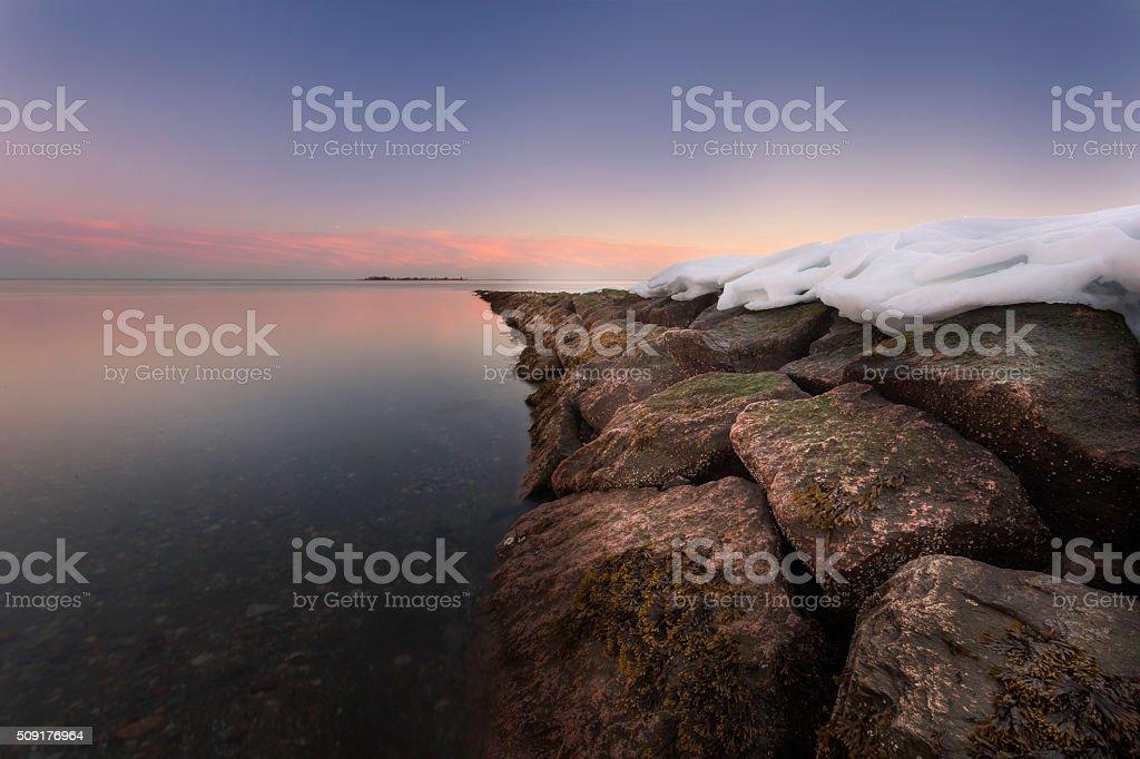 Snow On Rocks at Beach Purple Sky stock photo