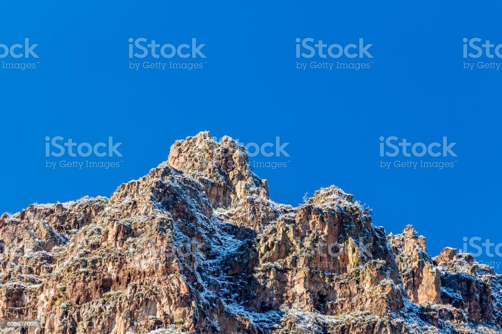 Snow on rocky mountain peak with blue sky; Sedona, Arizona stock photo