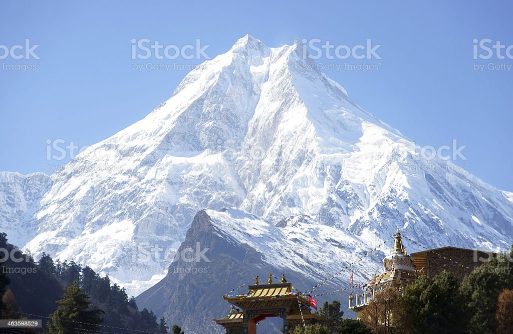 Snow peak, and the Buddhist monastery on its background royalty-free stock photo