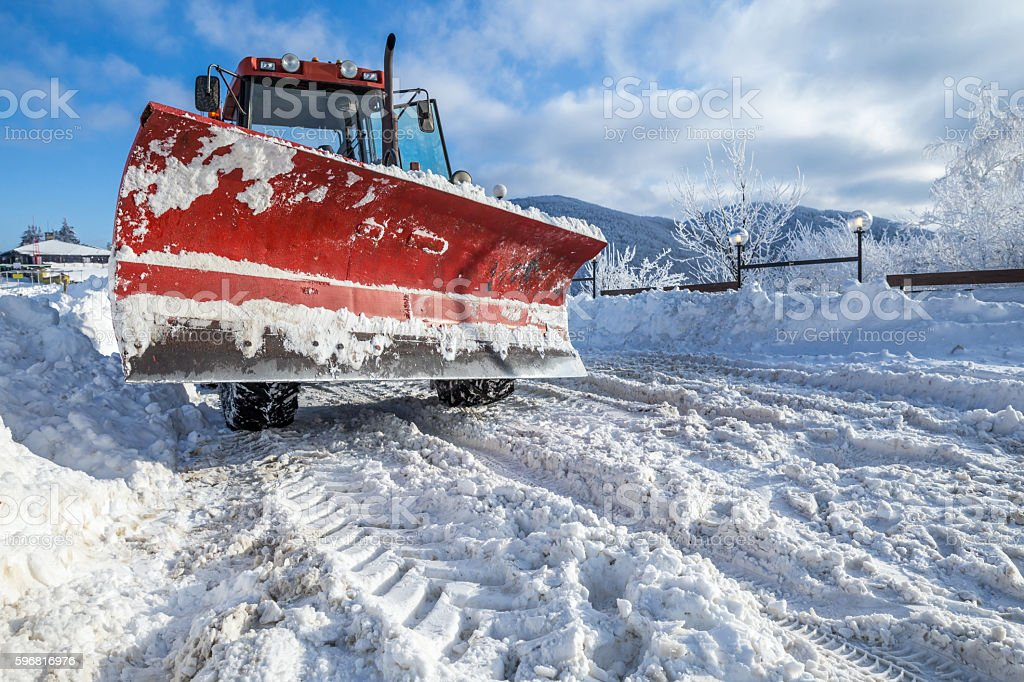 Snow plough machine on mountaon road stock photo