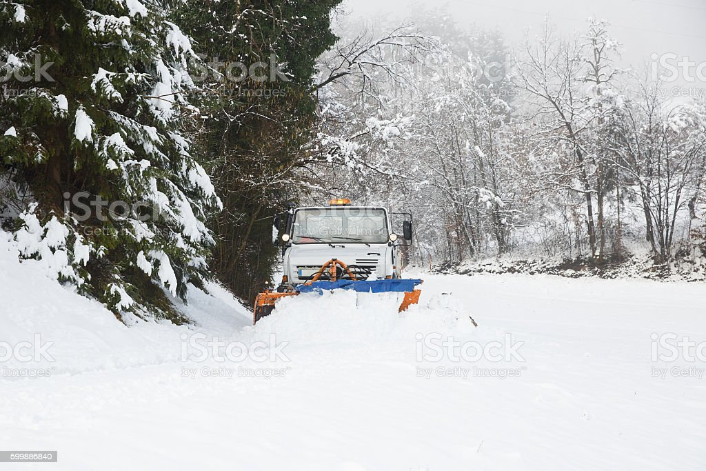 Snow plough making its way through the snowy country road stock photo