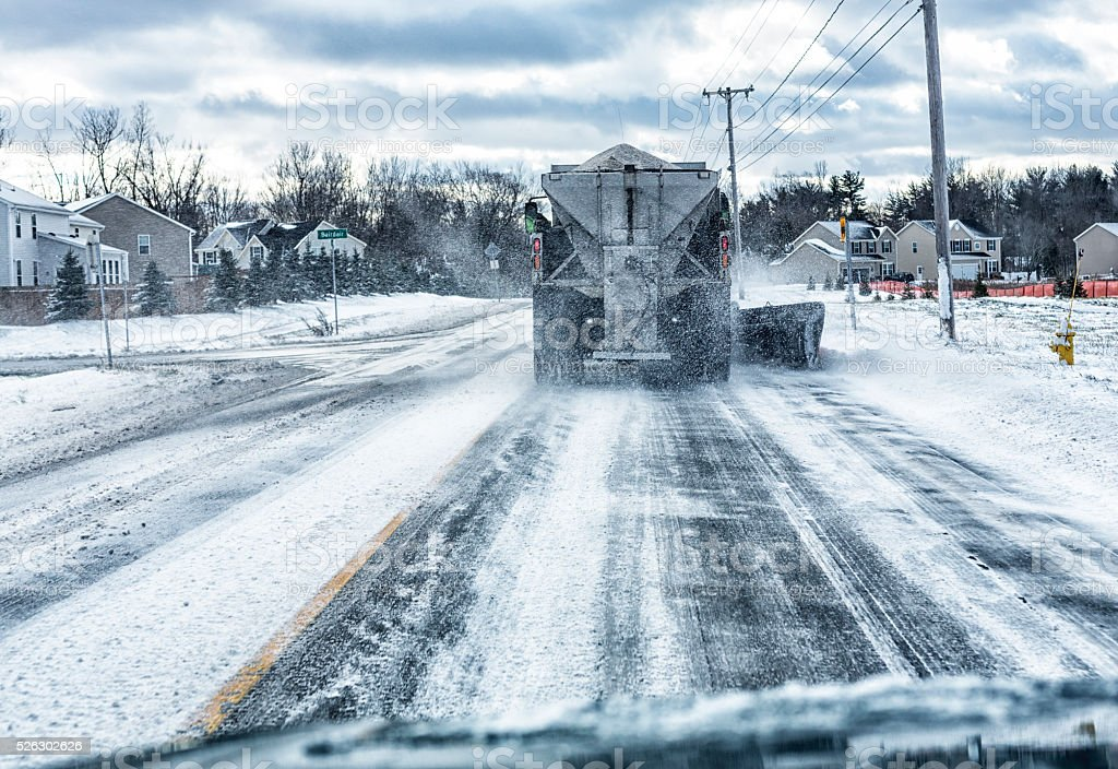 Snow Plow Dump Truck Passing Road Intersection Spreading Rock Salt stock photo