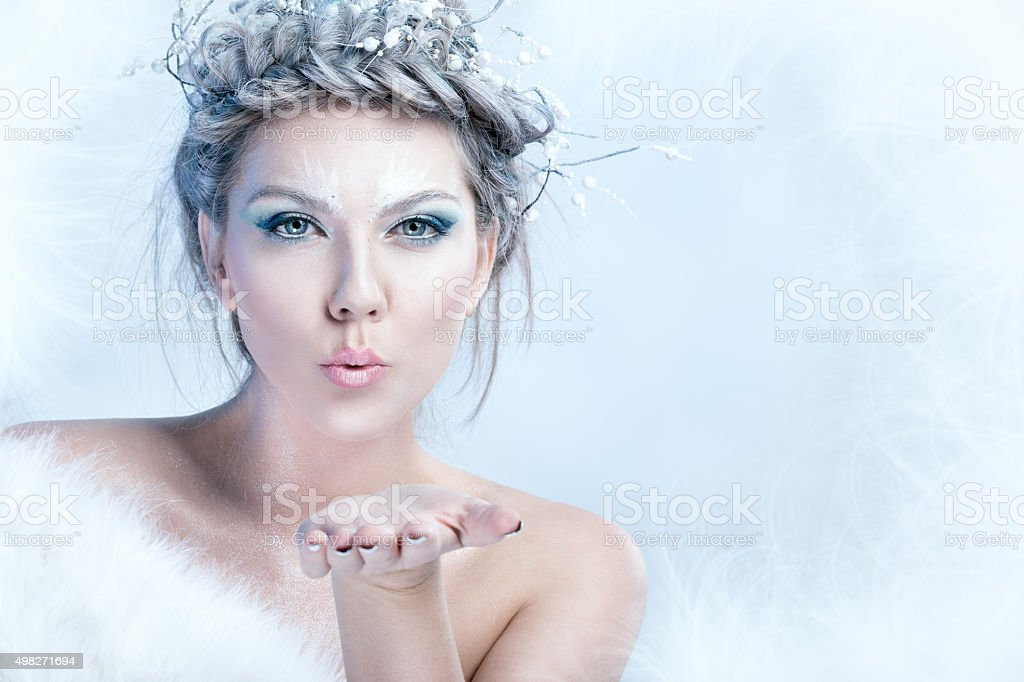 snow queen blowing in her hand stock photo