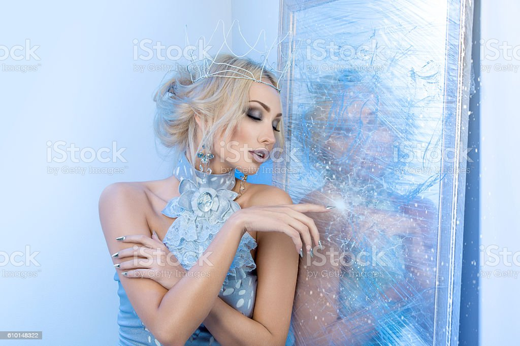 Snow queen near frozen mirror stock photo