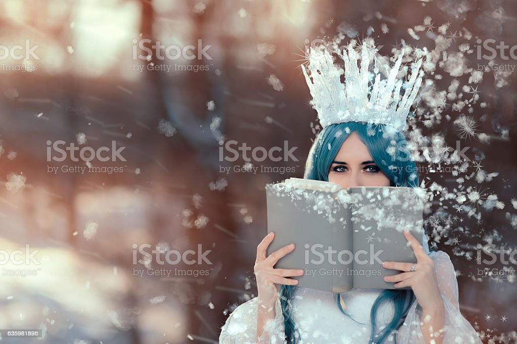 Snow Queen Reading Spell Book in Winter Fantasy stock photo