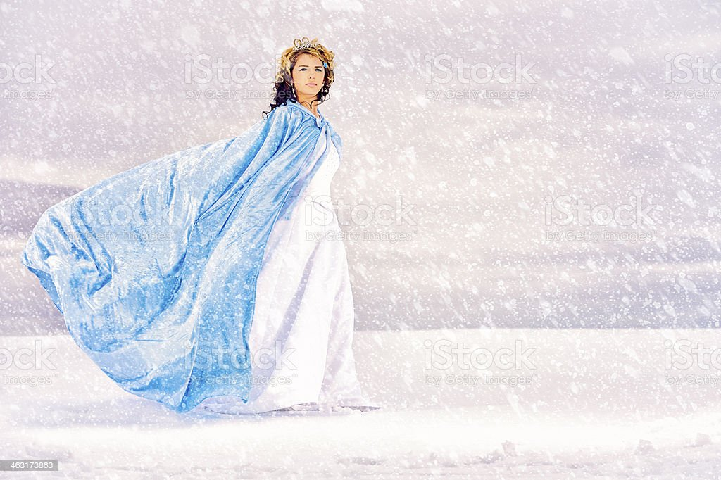 Snow Queen walking on a lake of ice while snow falls stock photo