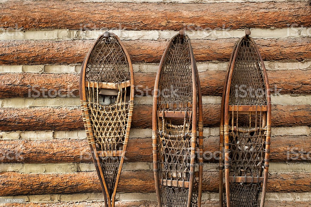 Snow shoes and a log cabin stock photo