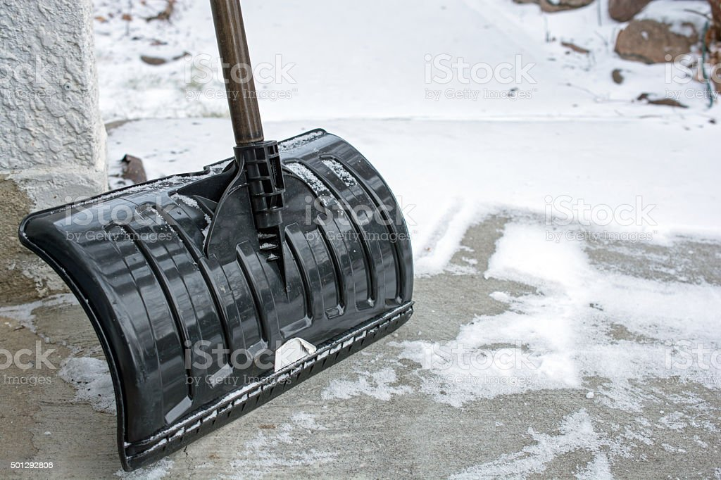 Snow shovel leaning against a building with snow background stock photo