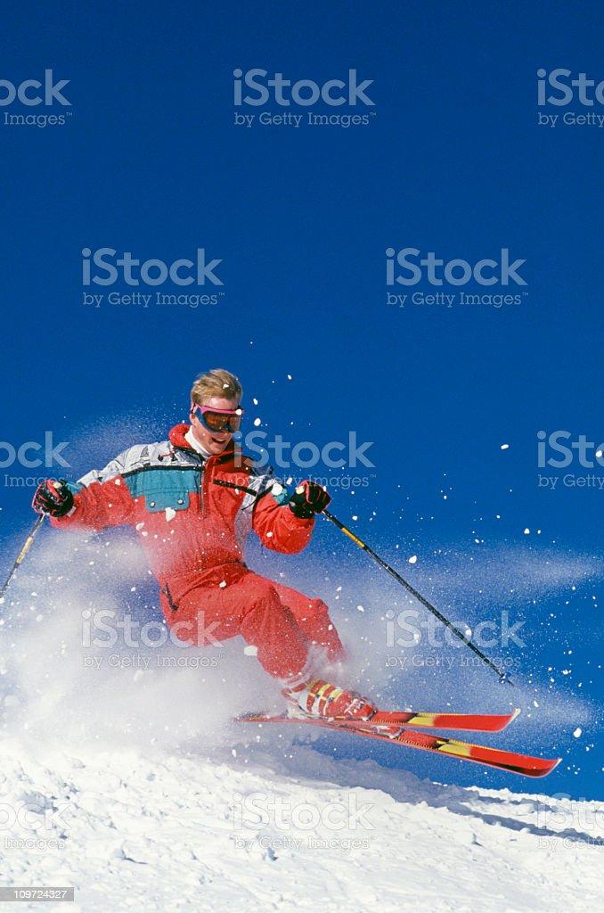 Snow Skier Flying Over Mogul Against Blue Sky stock photo