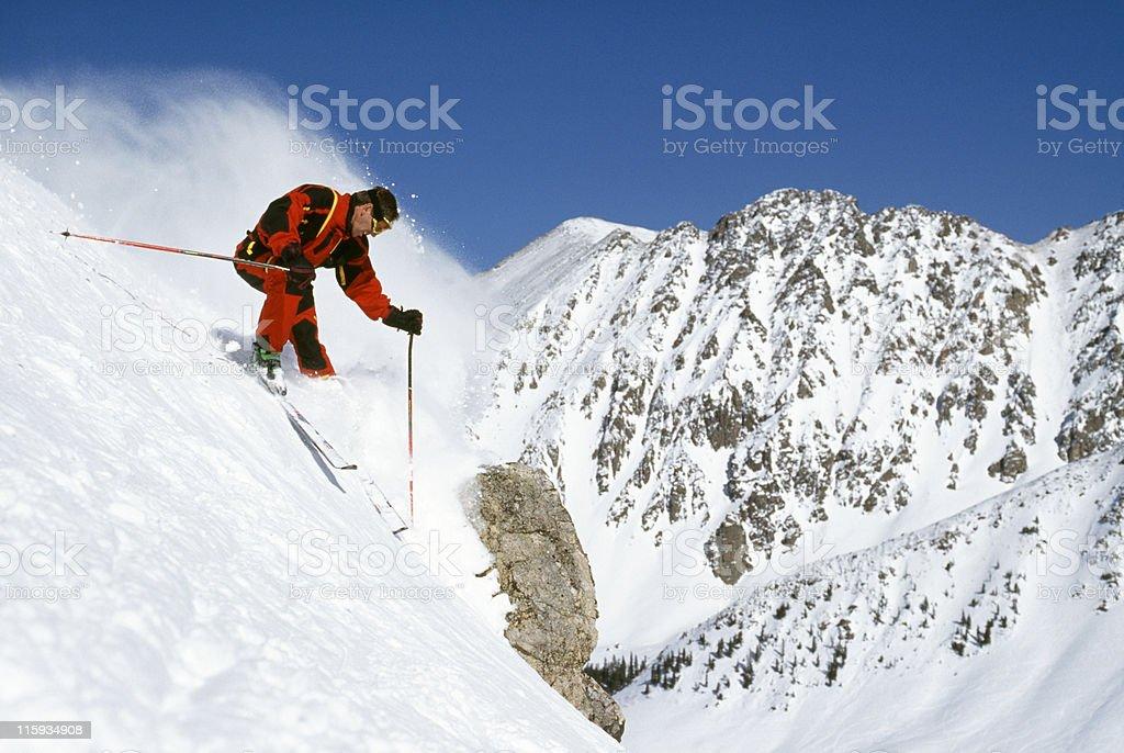 Snow Skier on Steep Grade with Mountain View stock photo