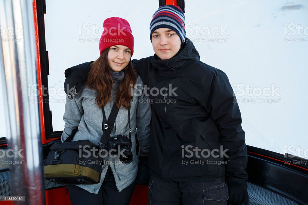 Snow skier   Teen boy and girl enjoying in cable car stock photo